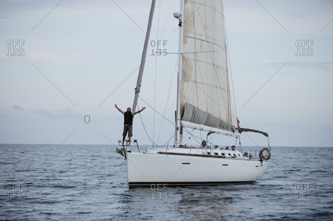 Female sailor with arms raised standing on sailboat in sea