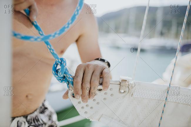 Close-up of sailor assembling mainsail on sailboat at harbor