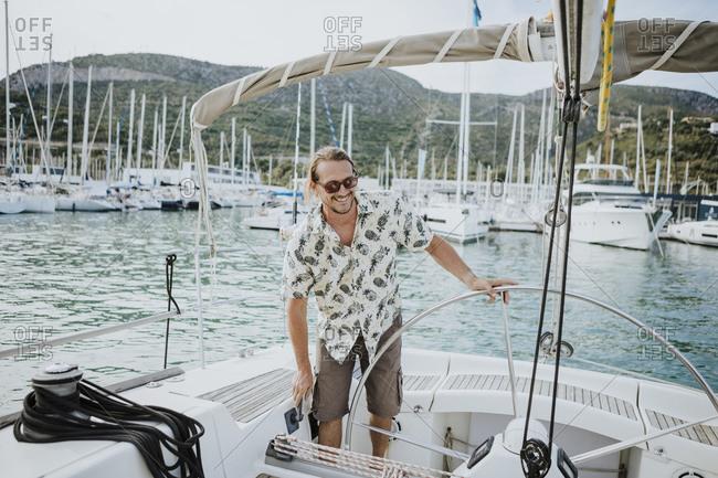 Happy sailor undocking sailboat at harbor