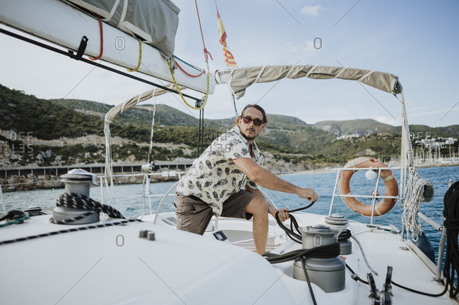 Male sailor maneuvering with winch in sailboat against sky