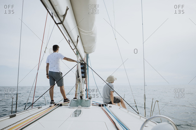 Friends looking at view while sailing on sailboat against sky