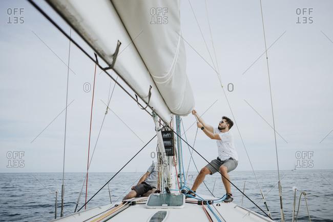 Sailor maneuvering setting the mainsail in sailboat against sky