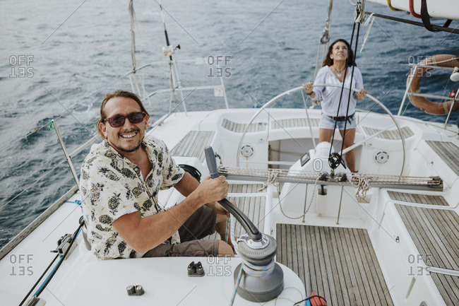 Man maneuvering with winch while woman driving sailboat in sea