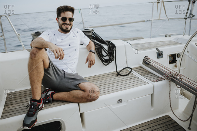 Smiling young man wearing sunglasses sitting in sailboat