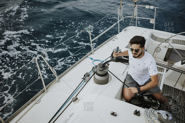 Young sailor wearing sunglasses maneuvering with winch in sailboat