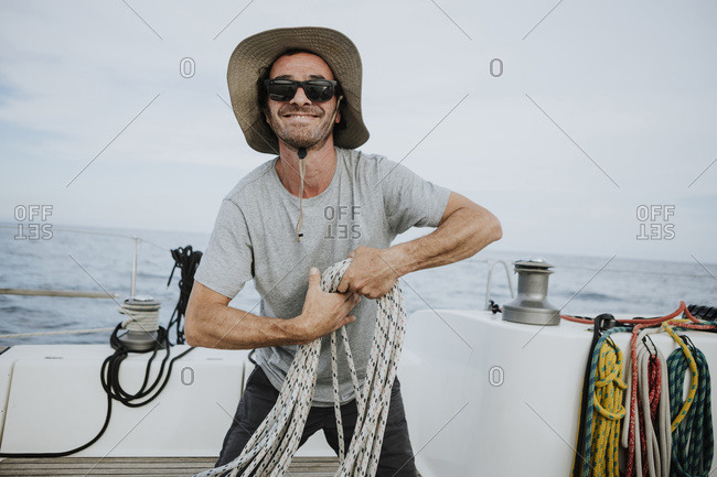 Smiling sailor wearing sunglasses and hat holding ropes in sailboat