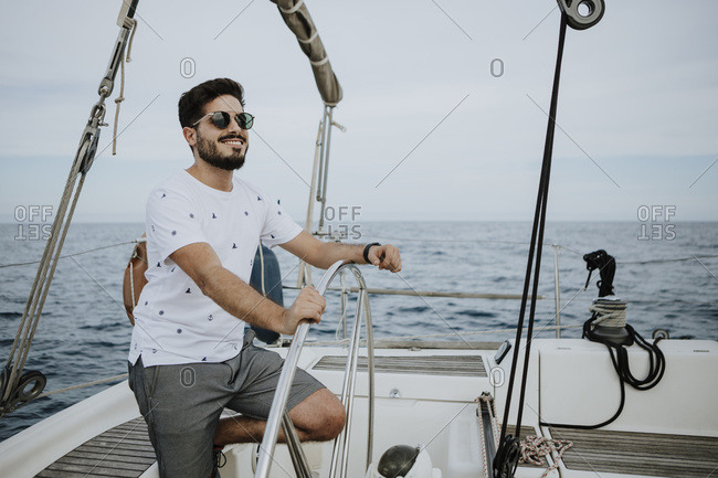Young sailor wearing sunglasses driving sailboat against sky