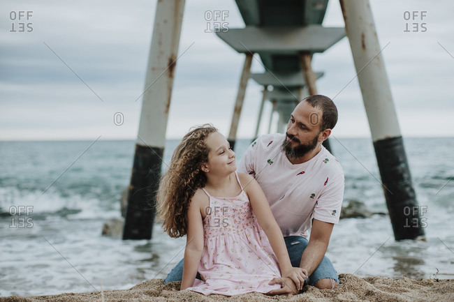 Father and daughter sitting on sand against pier at beach