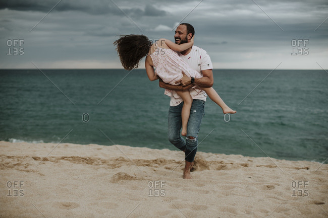 Happy father carrying daughter at beach