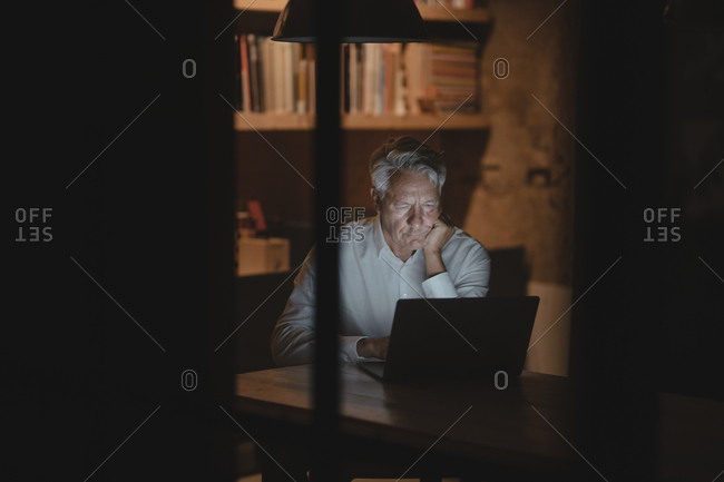 Senior businessman sitting in office- working late