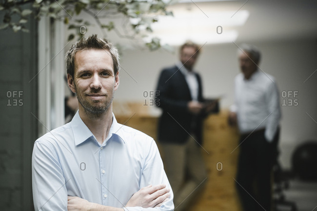 Businessman standing in open office door- with arms crossed - colleagues standing in background