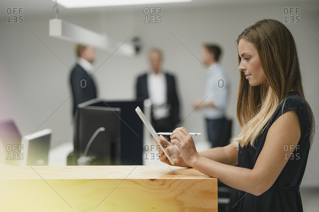 Businesswoman standing in office- leaning on wooden counter- using digital tablet