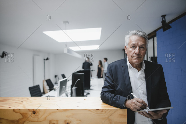 Senior businessman using digital tablet leaning on counter- coworkers working in office