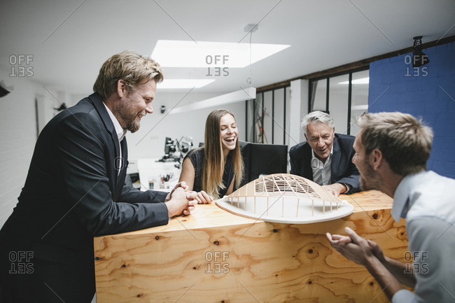 Successful business people looking at architectural model in office