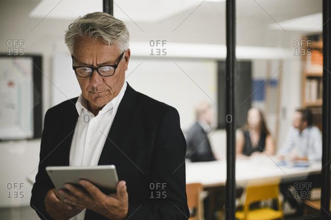 Senior businessman using digital tablet- coworkers working in background