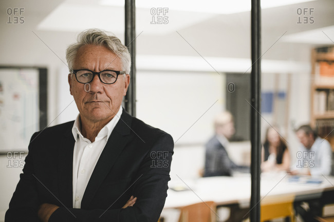 Portrait of a senior businessman with coworkers working in background