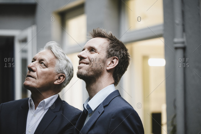 Two successful businessmen- looking at up- smiling