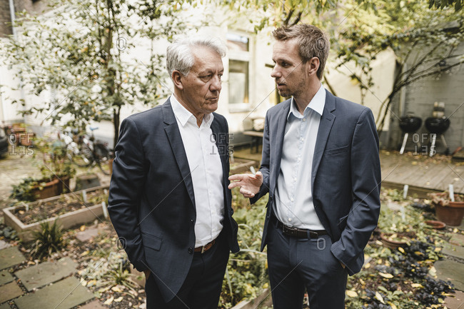 Two businessmen standing office backyard- discussing