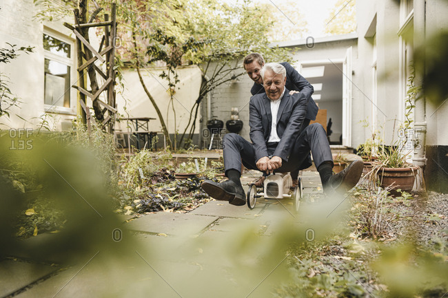 Businessman pushing senior partner on toy car through backyard