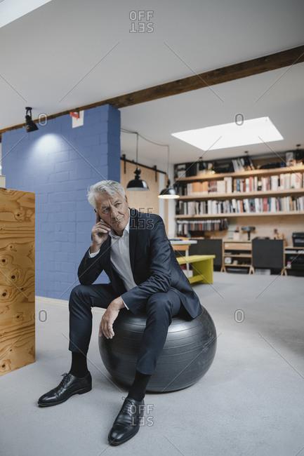 Senior businessman sitting on fitness ball- thinking
