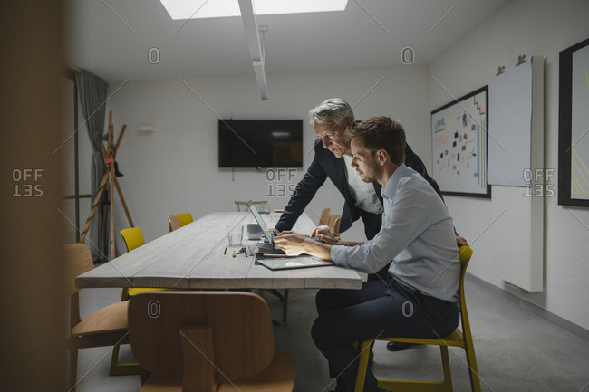Senior businessman supporting younger colleague in office