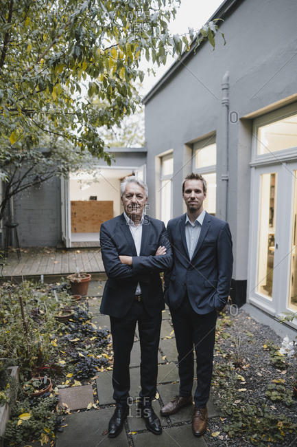 Two successful businessmen standing on backyard of their office