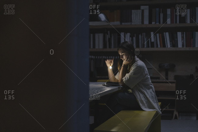 Young woman sitting in office- reading book at night with a torch