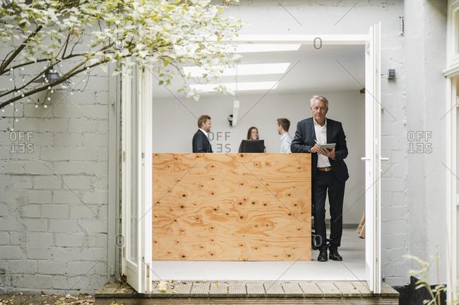 Senior businessman standing in office- using digital tablet- people working in background