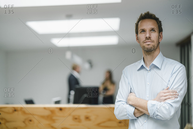 Businessman standing in open office door- with arms crossed - people working in background