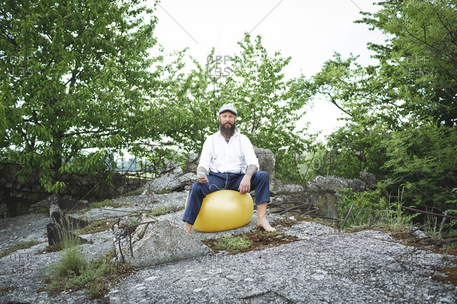 Bearded man listening music while sitting on fitness ball against trees