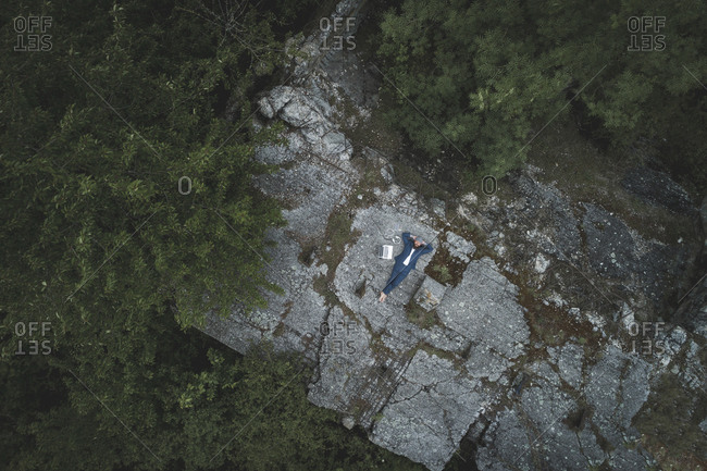 Drone shot of businessman wearing suit relaxing by laptop on land in forest