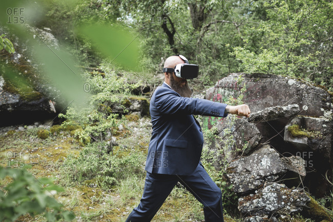 Businessman looking through virtual reality simulator practicing martial arts in forest