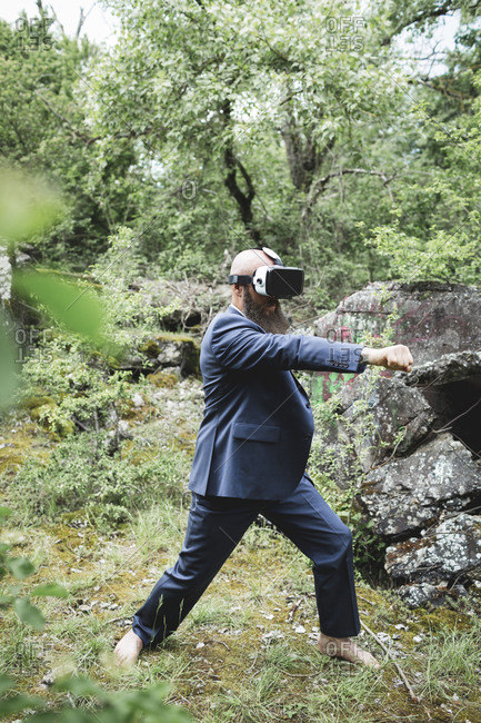 Businessman looking through virtual reality simulator practicing martial arts against trees in forest