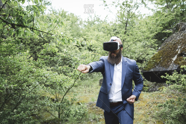 Businessman practicing martial arts while looking through virtual reality simulator against trees in forest