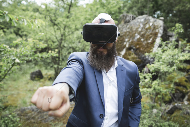 Close-up of businessman looking through virtual reality simulator while practicing martial arts in forest
