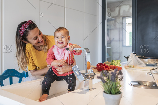 Smiling mother holding cute baby daughter playing with faucet in kitchen sink
