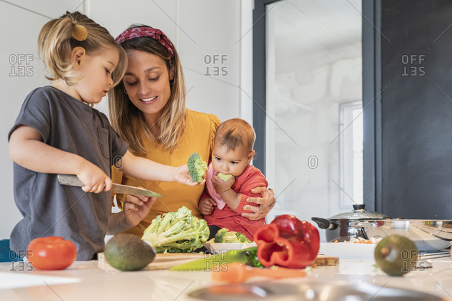 Mother holding baby girl while guiding daughter in cutting vegetables on kitchen island