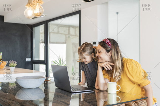 Smiling mother with daughter studying over laptop on table at home