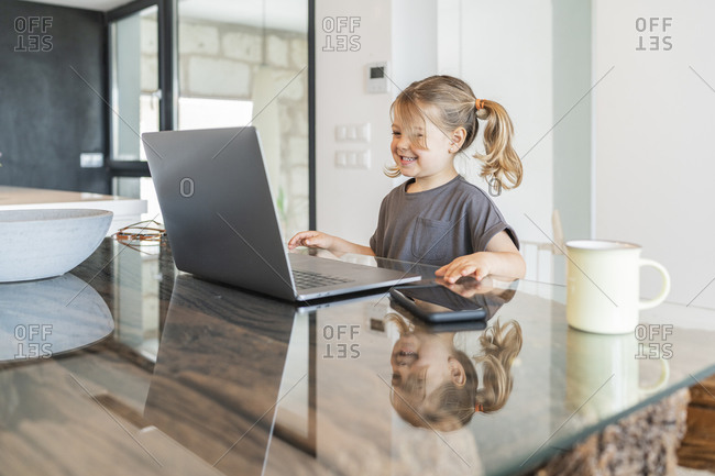 Smiling cute girl studying over laptop on table at home