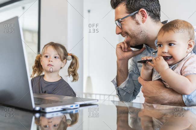 Man holding daughter talking over smart phone while girl looking at laptop on table