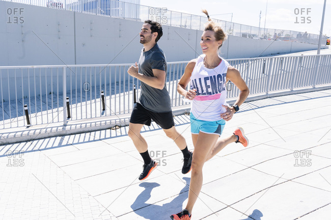 Happy fit couple jogging on city street during sunny day
