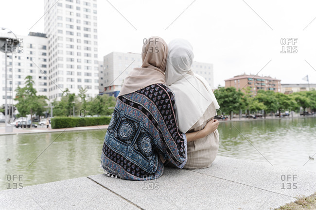 Muslim sisters sitting arm around on retaining wall by river in city