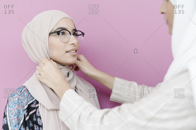 Muslim girl adjusting headscarf for sister against purple background