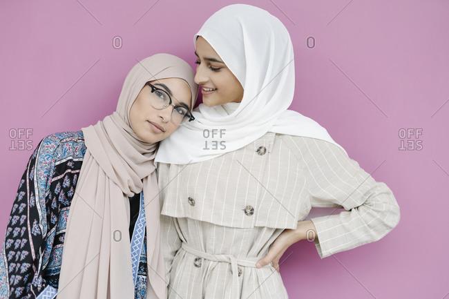 Muslim sisters standing against purple background