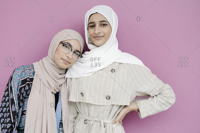 Muslim sisters standing together against purple background