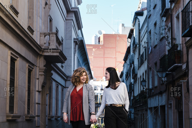 Lesbian couple holding hands while walking amidst buildings in city