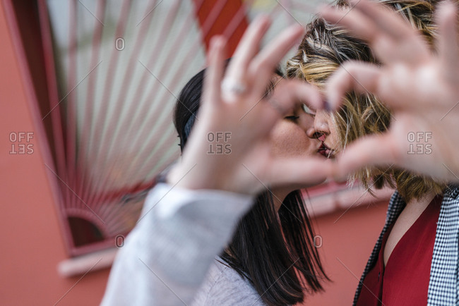 Close-up of lesbian couple gesturing heart shape with hands while kissing in city