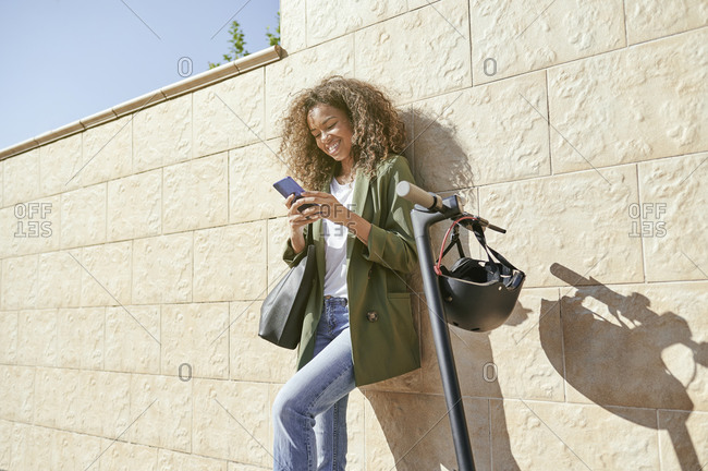 Happy woman using smart phone while standing by electric push scooter against wall