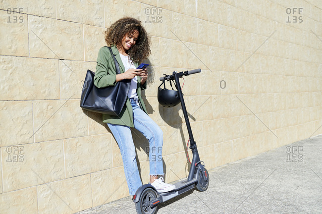 Happy woman using smart phone while standing with electric push scooter on sidewalk
