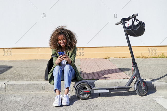 Happy young woman using smart phone while sitting on sidewalk by electric push scooter